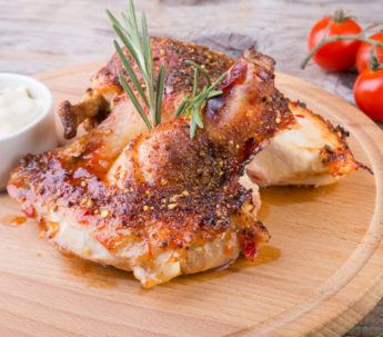 freshly cooked chicken breast artfully garnished and displayed on a wooden tray