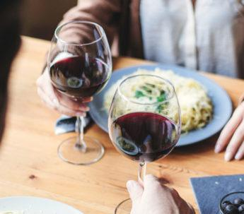 two people at a dining table with their meals and red wine